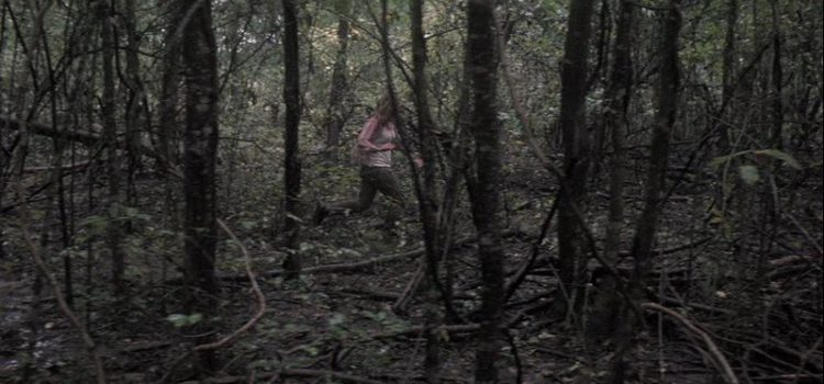 Woman running through dark woods
