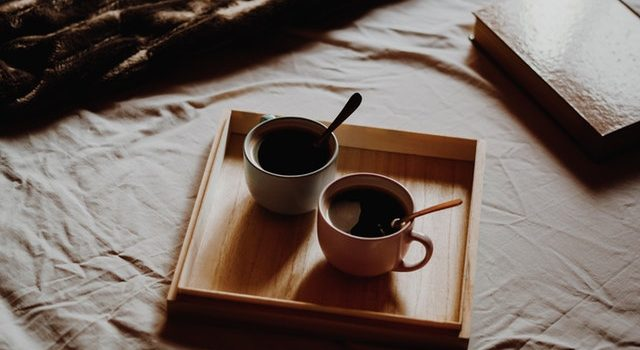 Cups of coffee on wood tray on a bed