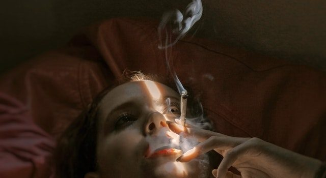 Woman in bed smoking cigarette