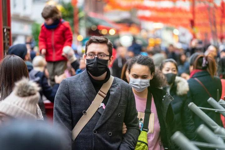 People walking down a busy street wearing face masks